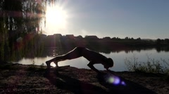 The Man Does Yoga on the Lake During Sunset. Pose Dog Upward. Stock Footage