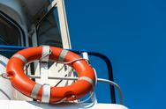 Orange lifebuoy on a white yacht Stock Photos