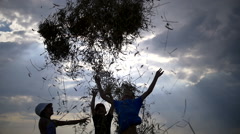 Children throw up hay on a background of clouds in the evening Stock Footage
