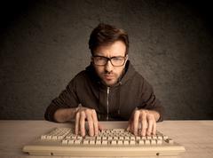 Computer geek typing on keyboard Stock Photos