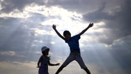 Boy with the girl jumping holding hands on a background of clouds in the evening Stock Footage