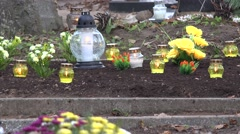 Tomb grave soil full of flowers and candles in religion holiday. 4K Stock Footage