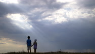 Boy with girl walking and holding hands on a background of clouds in the evening Stock Footage