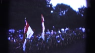 1966: shows a parade of boy scout troop marching down street with flags. Stock Footage