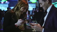Man and woman flirting at a bar exchange phone numbers Stock Footage