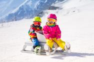 Kids on sleigh ride in the mountains Stock Photos