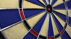 A moving shot of a dart board and a person hitting the bulls eye Stock Footage