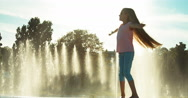 Girl child 7-8 years in sunglasses spinning on fountain background Stock Footage