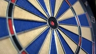 Side angle shot of a dart board and a person hitting the bulls eye Stock Footage
