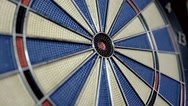 Front and a close-up shot of a dart board and a person hits the bulls eye Stock Footage
