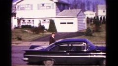 1966: he walk to open car door located at road put a briefcase behind seat Stock Footage