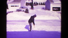 1966: man wearing a hoodie that is shoveling snow in the light wind HAGERSTOWN Stock Footage