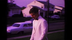1966: white suburban male in white suit and black bowtie entering car  Stock Footage