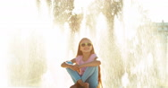 Child girl 7-8 years relaxing near fountain background at sunny day and looking Stock Footage