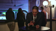 Well dressed young man in a nightclub holds his drink up and smiles Stock Footage