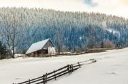 Woodshed on the hillside in winter mountains Stock Photos