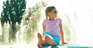 Girl 7-8 years sitting near fountain at sunny day. Child in sunglasses smiling Stock Footage