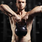 Fitness man doing a weight training by lifting heavy kettlebell Stock Photos