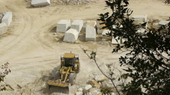Marble blocks and front loader machine in stone quarry Stock Footage