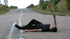 The fire eater, spitting fire, lying on the pavement Stock Footage