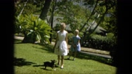 1964: girls are playing with their dog HAWAII Stock Footage