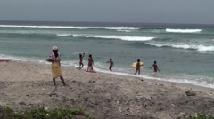 A group of young naked boys playing with broken surf board in the ocean. Stock Footage