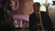 Young man hands his business card to another man at a nightclub Stock Footage