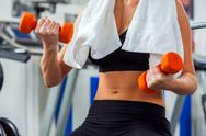 Woman hands keeps dumbbells at gym. Stock Photos