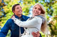 Guy in love keeps girl his arms in autumn park. Stock Photos