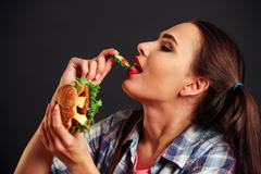 Girl eating hamburger with appetite . Stock Photos