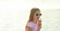 Girl 8 years old eating ice-cream on fountain background at sunny day Stock Footage
