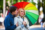 Loving couple on date under umbrella in good autumn day. Stock Photos