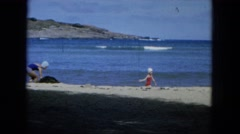 1964: two girls enjoy the sandy beach on a windy summer day. HAWAII Stock Footage