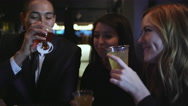 A group of friends standing at a bar holding their drinks and talking Stock Footage