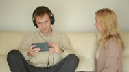 Woman yells at man with headphones. Husband plays on the smartphone Stock Footage