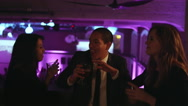 A group of friends in the balcony of a nightclub holding drinks and dancing Stock Footage