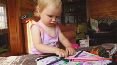 Sweet little girl draws with colored pencils Stock Footage