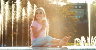 Girl eating ice-cream on fountain background at sunny and hot day Stock Footage