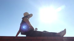 Girl in Cowboy Hat Drinking Coffee. he Resting on the Sun Lights. Stock Footage