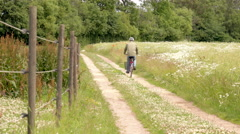 Man with helmet on bicycle. Riding a bike on rural road. Stock Footage