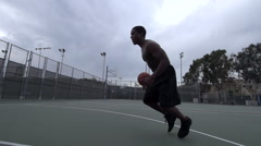A young man playing basketball on a rainy day. Stock Footage