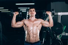 Muscle man doing bicep curls Stock Photos