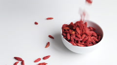 Putting goji berries in white porcelain bowl. White background. Stock Footage