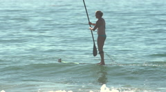 A woman sup stand-up paddleboard surfing at the beach. Stock Footage