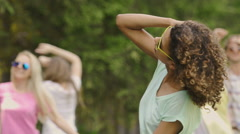 Young female singer dancing in music clip, backup dancers partying on background Stock Footage