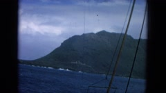 1964: showing the tip of land from boat going around a mountain at seaside. Stock Footage