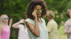 Flirty girl with curly hair dancing, smiling to camera. Friends partying in park Stock Footage