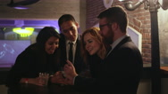 A group of friends in a nightclub looking at pictures on a cell phone Stock Footage