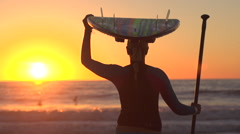 A silhouetted portrait of woman sup stand-up paddleboard surfing at the beach at Stock Footage