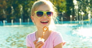 Close up portrait girl blowing soap bubbles on fountain background at sunny Stock Footage